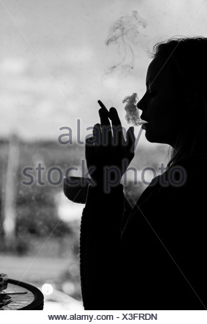 Silhouette of an attractive woman smoking cigarette - Stock Photo