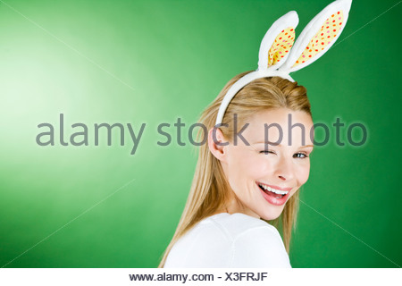 A young blonde woman wearing bunny rabbit ears, winking - Stock Photo