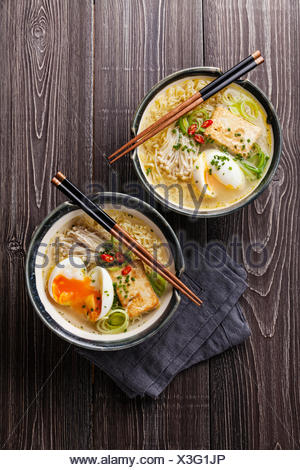 Asian Miso ramen noodles with egg, tofu and enoki in bowls on gray wooden background - Stock Photo