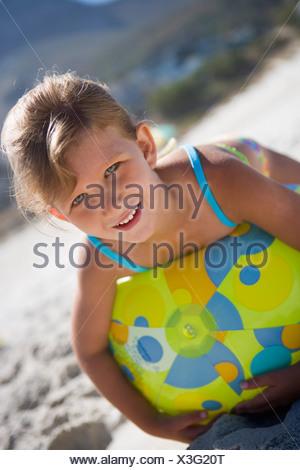 Girl 5 7 lying on green beach ball on sandy beach smiling close up portrait tilt - Stock Photo