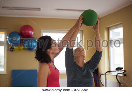 Female therapist assisting senior woman with ball - Stock Photo