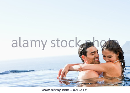 Couple hugging in the pool - Stock Photo