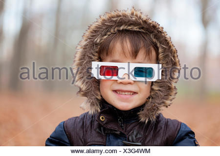 Portrait of smiling little boy wearing hooded jacket and 3D glasses - Stock Photo