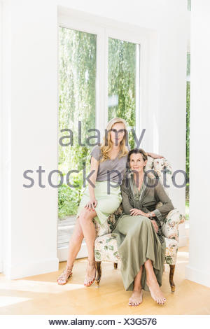 Portrait of senior woman and daughter sitting on armchair in living room - Stock Photo
