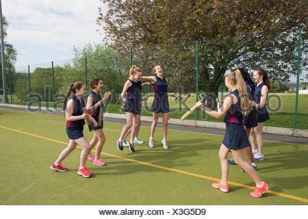 Group of girls on sports field with rounders bats
