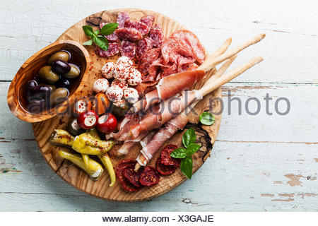 Antipasto Platter Cold meat plate with grissini bread sticks on wooden background - Stock Photo