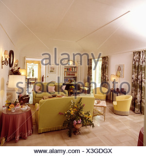 Large floral arrangement behind sofa in white eighties-style country living room with white flooring - Stock Photo