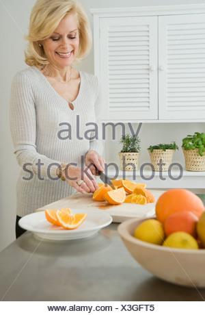 Senior woman cutting oranges - Stock Photo