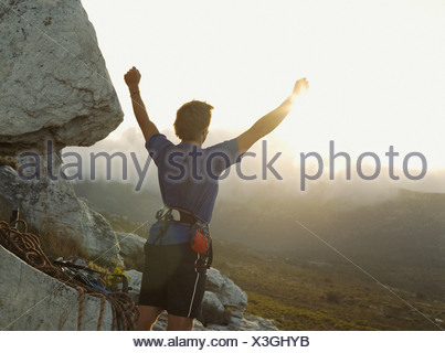 A victorious mountain climber with his arms up in the air - Stock Photo