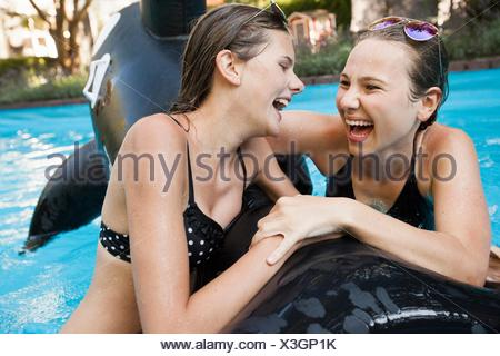 Two teenage girls holding onto inflatable fish in swimming pool - Stock Photo