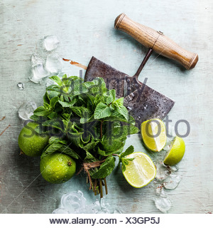 Ingredients for making mojitos Ice cubes, mint leaves and lime on blue background - Stock Photo