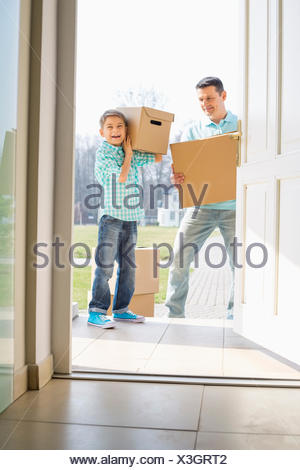 Happy father and son with cardboard boxes entering into new house - Stock Photo