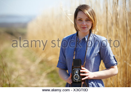 Close up portrait of young woman holding camera - Stock Photo