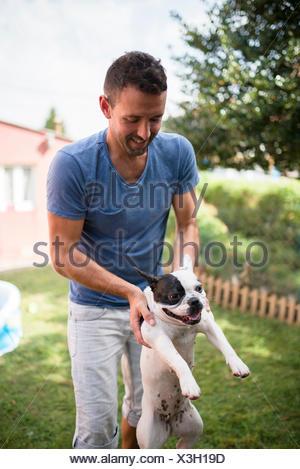 Man carrying a French bulldog in a garden - Stock Photo