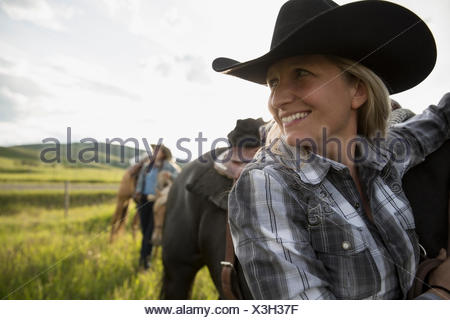 Close up smiling female rancher with horse looking away - Stock Photo
