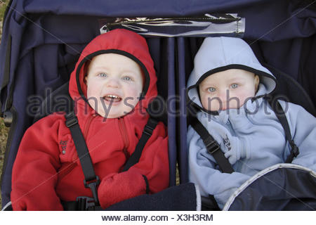 16 month old twin boys sitting in pram in winter - Stock Photo
