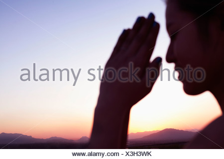Serene young woman with eyes closed and hands together in prayer pose in the desert in China, focus on background - Stock Photo