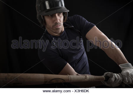 Portrait of a baseball player swinging a bat - Stock Photo