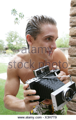 Young man in bathing suit holding camera. - Stock Photo
