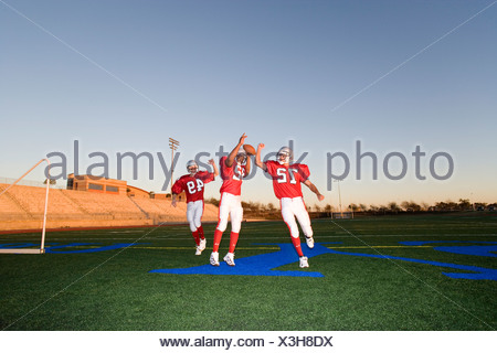 Three American football players, in red football strips, celebrating touchdown on pitch during competitive game at sunset - Stock Photo