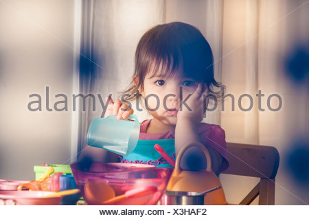 Sad girl playing with toys
