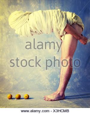 Profile Shot Of Man Wrapped In Bandage Bending Towards Oranges - Stock Photo