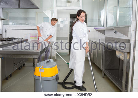 couple cleaning kitchen surfaces and cupboards together - Stock Photo
