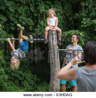 Mother photographing children playing on monkey bar - Stock Photo