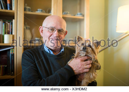 Portrait of senior man with his Yorkshire terrier at home - Stock Photo