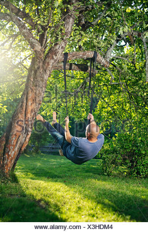 Man swinging on tree swing - Stock Photo