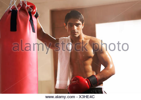 Portrait of young male boxer by punching bag at gym - Stock Photo
