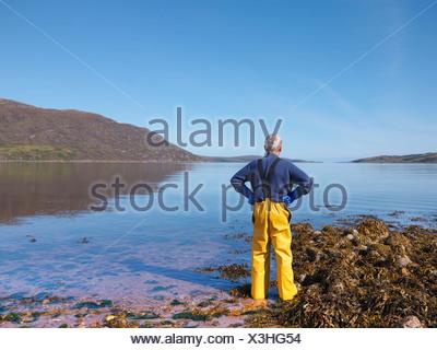 Fisherman surveying lake - Stock Photo