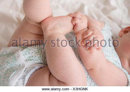 Baby girl (12-17 months) lying down with hands on feet - Stock Photo