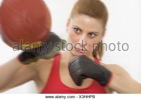 Female boxer hitting punching bag - Stock Photo