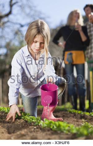 Girl watering plants in garden - Stock Photo
