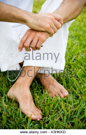 cropped image man's legs and bare feet on grass - Stock Photo