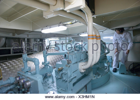 Engineer working in ships engine room - Stock Photo