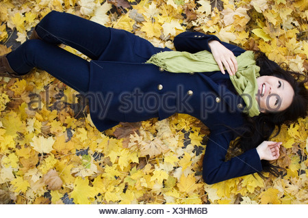 Woman laying in autumn leaves - Stock Photo