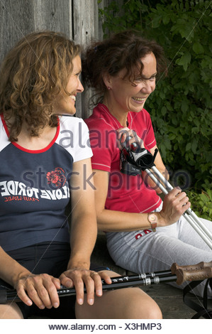 2 two women rest from Nordic Walking on a bench in front of a barn - Stock Photo