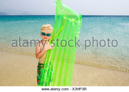 Young boy at the beach with an inflatable raft. - Stock Photo