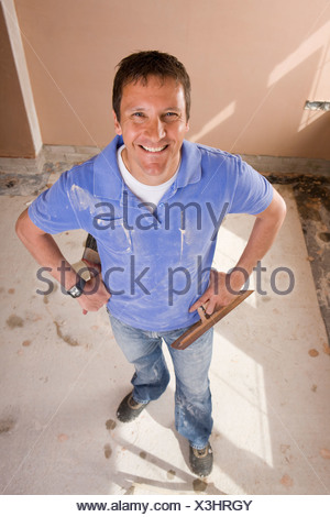Smiling man holding plastering trowel - Stock Photo