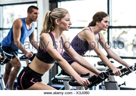 Fit people working out at spinning class - Stock Photo