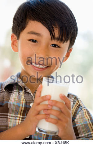 Young boy indoors drinking milk smiling - Stock Photo