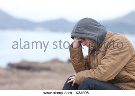 Worried teenager guy on the beach in winter - Stock Photo