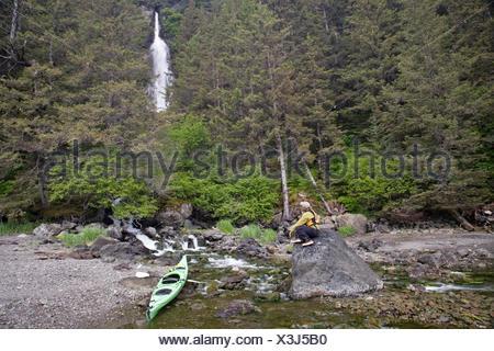 Sea Kayaker Sits On A Rock And Enjoys A Unnamed Waterfall, Kachemak Bay State Park, Kenai Peninsula Alaska During Summer - Stock Photo