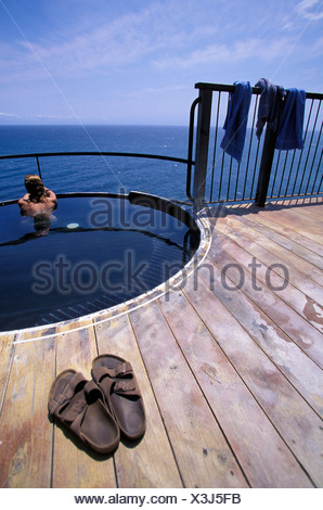 A woman in a hot spring by the ocean in Esalen, California. - Stock Photo