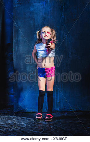 Little girl pointing in toy gun - Stock Photo
