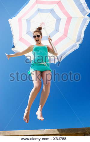 Woman holding beach umbrella and jumping off ledge - Stock Photo