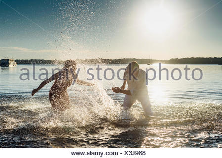 Couple squirting each other with water - Stock Photo