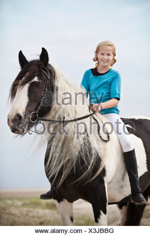 Young horserider riding bareback on a mare, pony, Tinker, black and white chequered, in the dunes at the beach, Borkum - Stock Photo